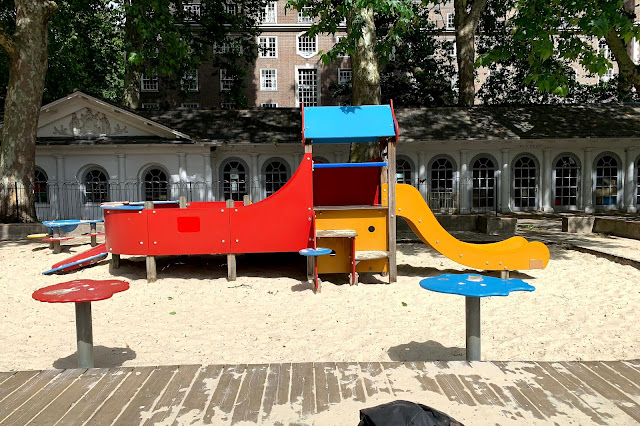 A colourful playframe with slide for preschoolers in a sand pit at Coram's Fields London