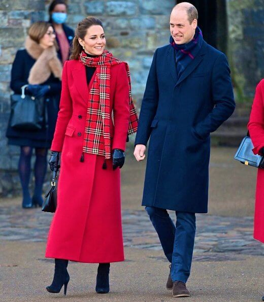 Kate Middleton wore a tartan pleated skirt from Emilia Wickstead, yellow gold hoops from Spells of Love. Alexander McQueen red coat. Grace Han bag