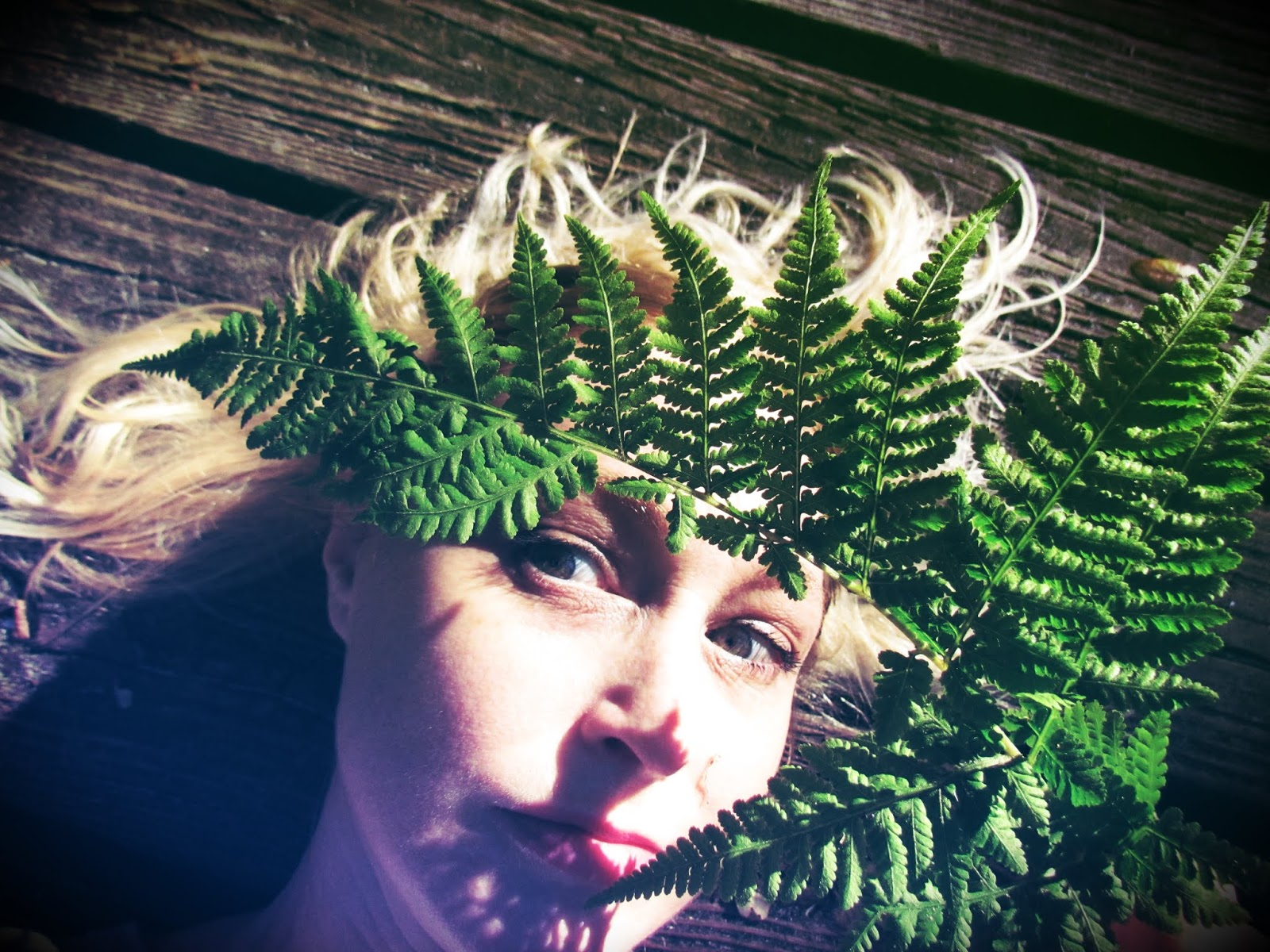 A woman laying on a woodland boardwalk in the clearing with a fern headdress