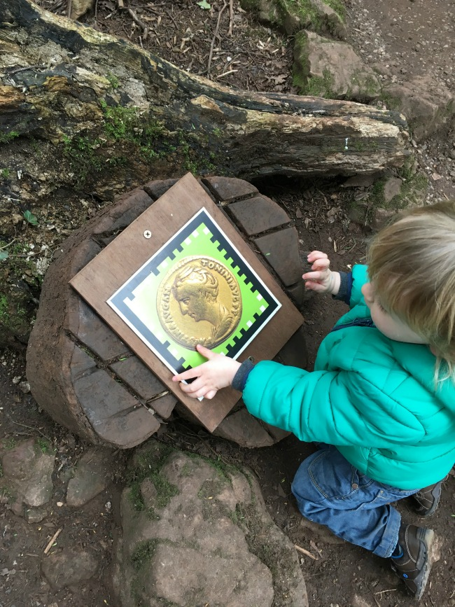 toddlet knelt down next to a log with a large picture of a Roman coin fixed to it