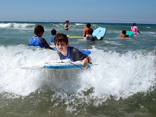 Boy boogie boarding the waves with other kids swimming in the background at Zuma Beach.