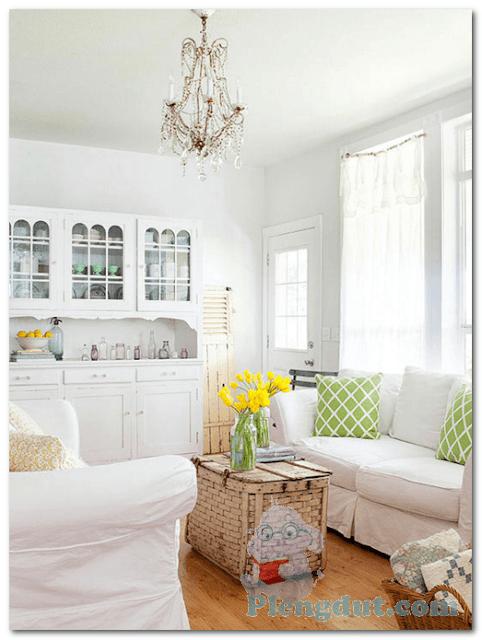Ide 14: Lantai rumah dari kayu dan dekorasi full putih mulai dari cat, sofa, rak lemari, serta kombinasi kreatif bantal berwarna hijau lemon dan hiasan bunga membuat tampilan ruangan menjadi fresh