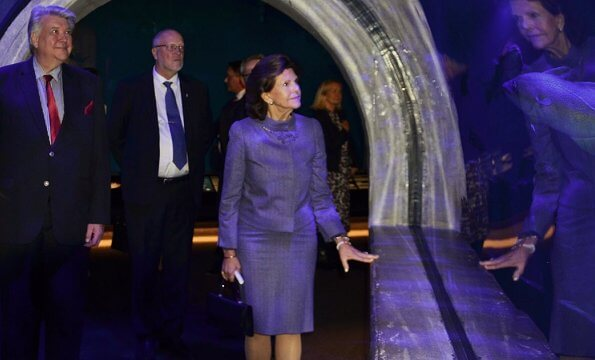Queen Silvia wore and blue jacket and skirt, skirt suit. She is wearing gold earrings and gold bracelet