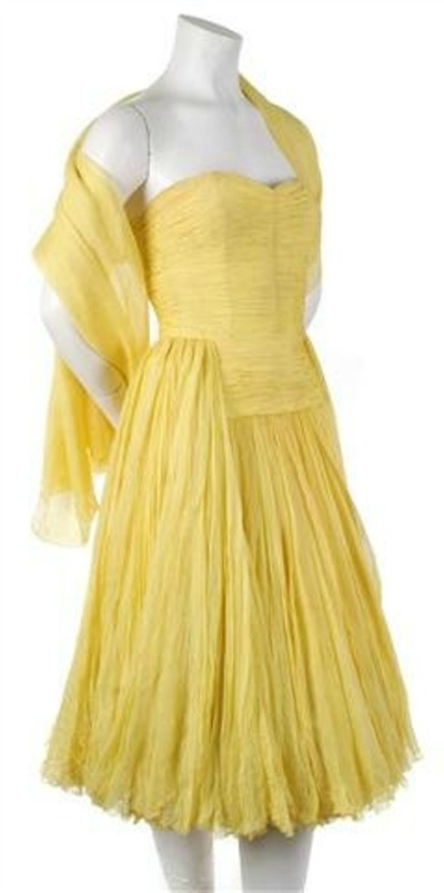 Yellow cocktail dress with pleats and tucks designed by Jean Dessés displayed on mannequin