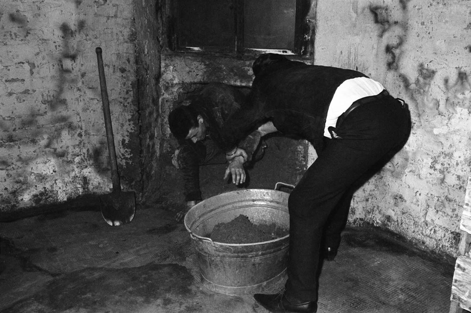 One of six West Berliners who dug a 20-inch-wide tunnel under a border street to East Berlin crawls out sometime over the weekend of June 8–10, 1962. Sixteen East Berliners, relatives of the diggers, came through the tunnel dragging an infant behind them in a wash basin. The tunnel was believed to have been discovered in early June 12, a few hours after the 17 reached the West.
