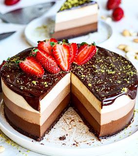 Pastel redondo de tres chocolates con fresas por encima.