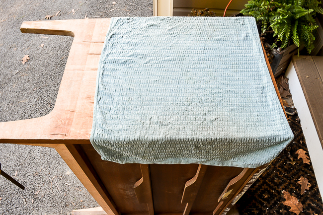 Using a hot damp towel to help remove damaged veneer