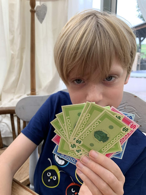 Bank attack game. Child holds millions of notes
