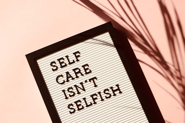 """A quote on a card which says,""""Self-care is not selfish"""" with a light pink background."""