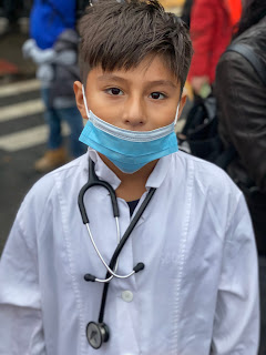 A young boy is dressed up as a doctor for Halloween.