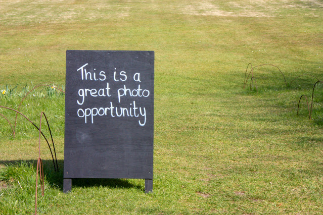 A large blackboard easel on a lawn with large lettering saying: this is a great photo opportunity.
