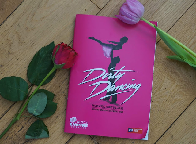 flat lay image for playbill for dirty dancing - the classic story on stage with two pink flowers framing the programme