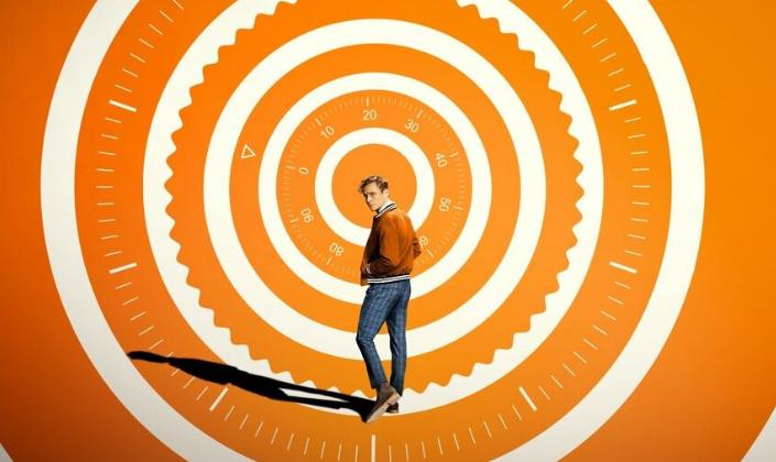 Imagem: o pôster do filme, um fundo alaranjado com uma espiral branca em que se vê os códigos de um cofre e no centro, o personagem principal, Ludwig, um homem branco com cabelos loiro-alaranjados, em um casaco laranja com jeans azul com riscas quadriculadas, olhando para trás e projetando uma sombra.