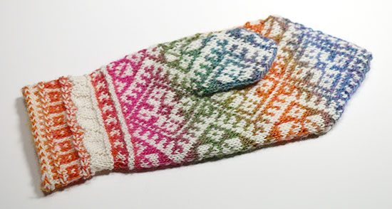 Palm of hand knit wool colorwork mitten showing outer thumb stitches on a white background.