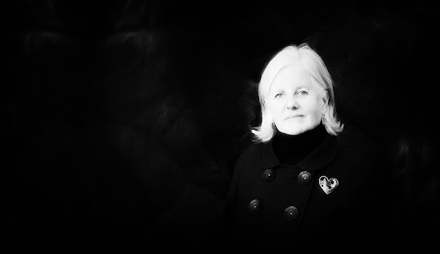 Black background, blonde woman wearing black coat with hear brooch