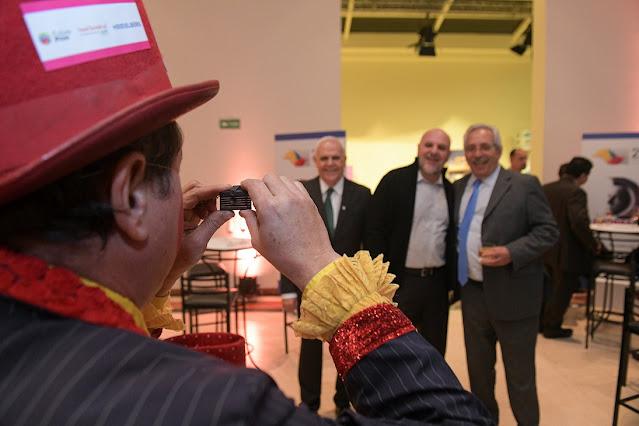 Artistas circenses de Humor e Circo interagindo em evento de premiação da Abigraf, na imagem o artista Palhaço tirando uma foto dos convidados com uma mini camera e eles rindo.
