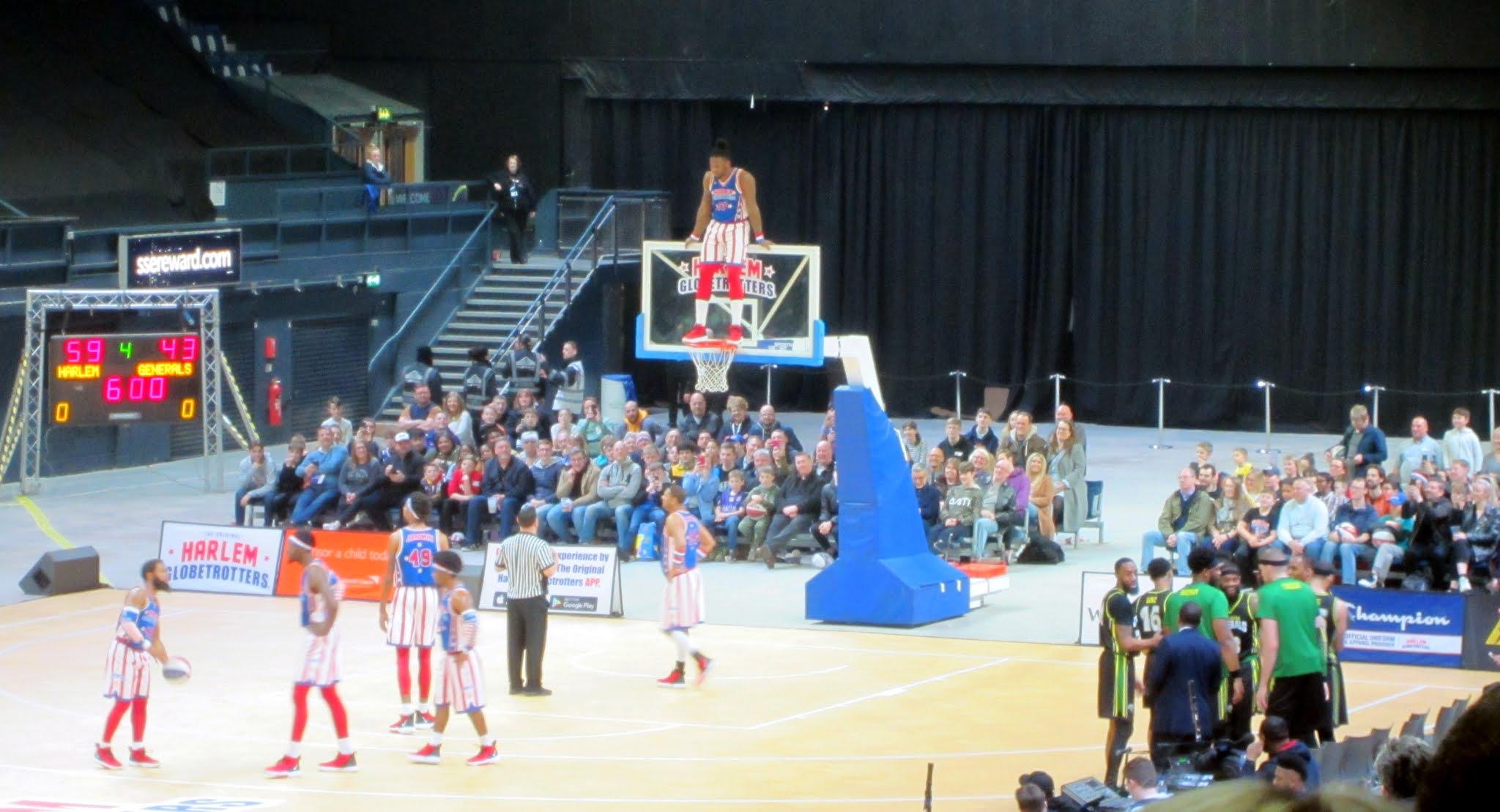 A Harlem Globetrotters player stands on the basket