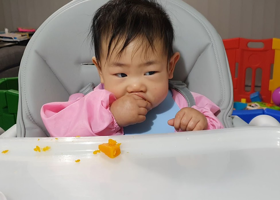 My 7-month-old baby feeding herself steamed pumpkin.