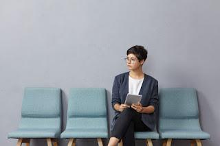 mulher de cabelo curto e formal aguardando para entrevista de emprego