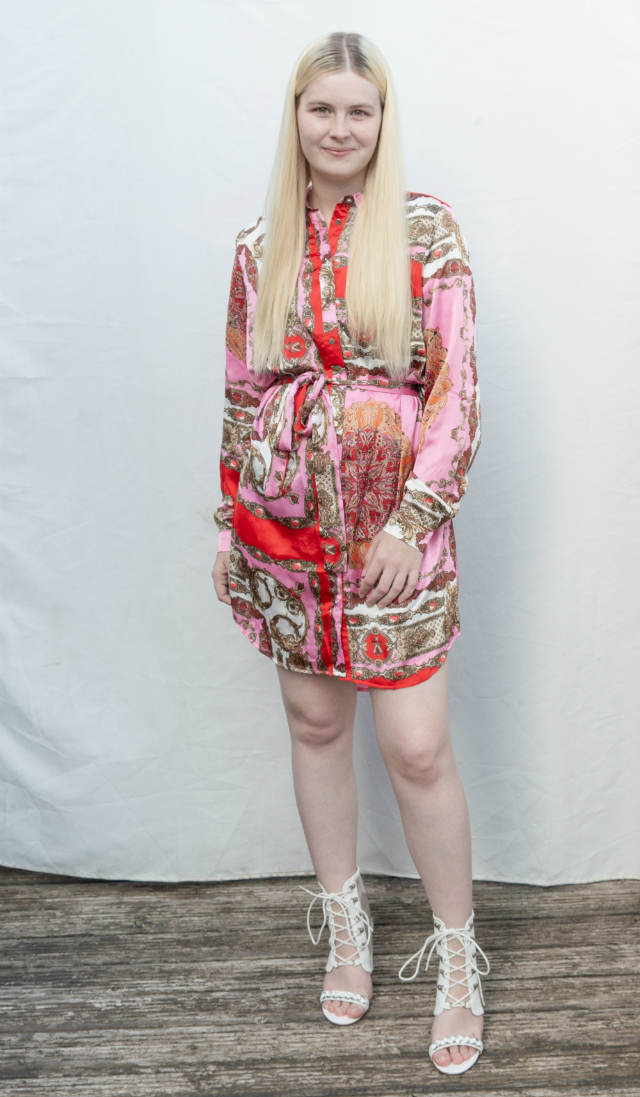 Wearing a pink and red shirt dress with ornate print and white shoes.