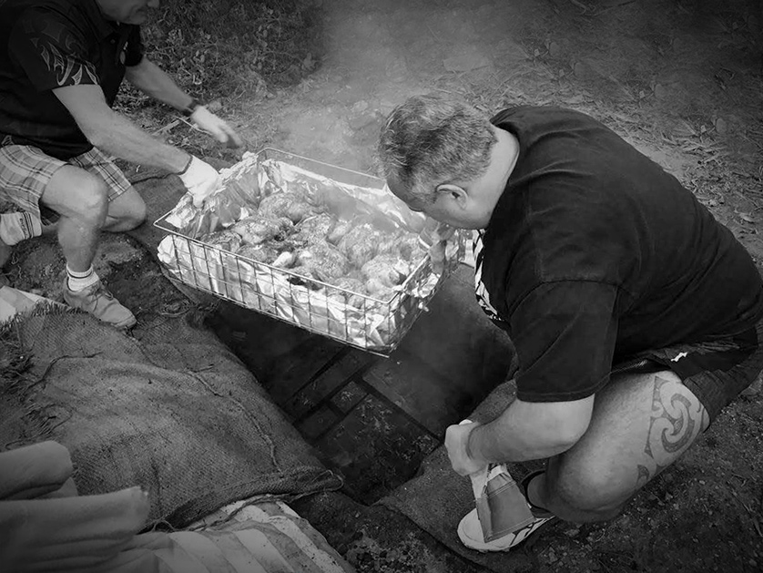 A  hangi in progress, with food being placed underground.