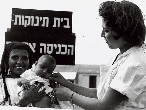 אחות לצד יוצאת תימן ובנה, בפתח בית תינוקות במחנה עין שמר
