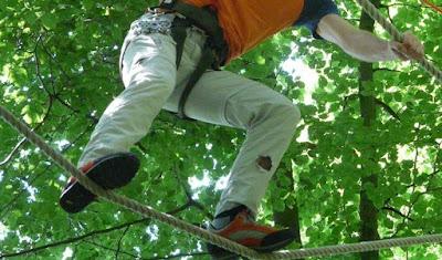 Bild på ben och fötter på person som balanserar på en repgång med trädtoppar i bakgrunden.