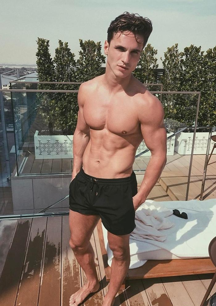 handsome-shirtless-male-model-huge-muscle-pecs-hairless-body-dark-shorts-luxury-lifestyle