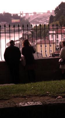 pessoas na grade observando o rio Douro e a Ponte da Arrábida