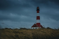 Lighthouse in storm - Photo by Thomas Grams on Unsplash