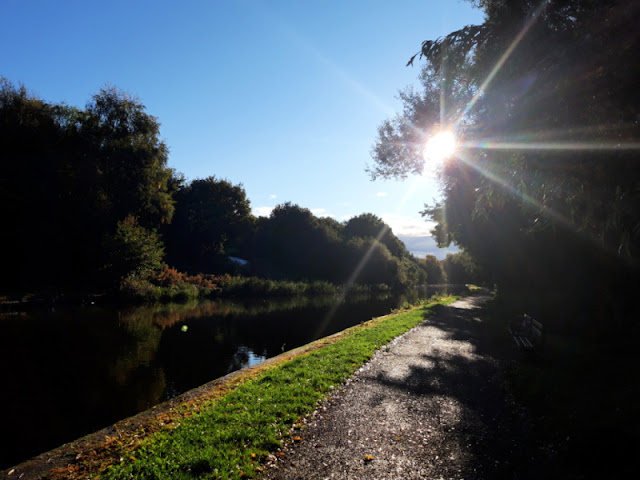 A towpath next to a disused canal.  The sky is blue and the sun is coming through the trees.  The leaves are shades of gold and brown, reflecting off the water