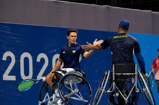 De frente está o tenista Gustavo Carneiro, que em sua cadeira de rodas, cumprimenta o parceiro de dupla, Daniel Rodrigues, também na cadeira, após a disputa de um ponto
