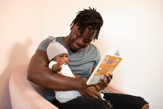 Picture of seated Black man holding his child, and holding a children's book. Photo from nappy.co
