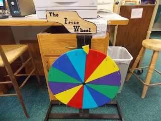 A spinning prize wheel, with multicolored pie-shaped sections and a pointer, sitting in the the library under a computer table