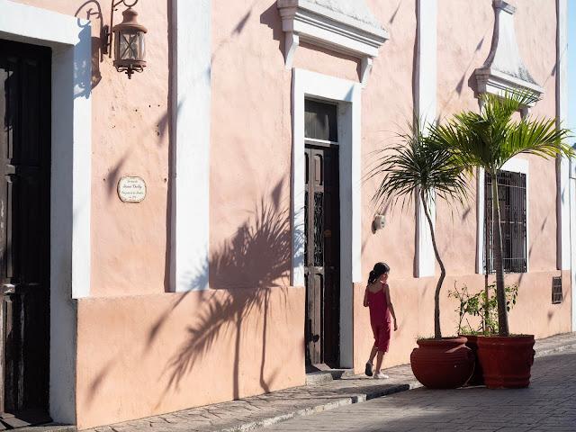 Niña paseando frente a una fachada colonial rosa