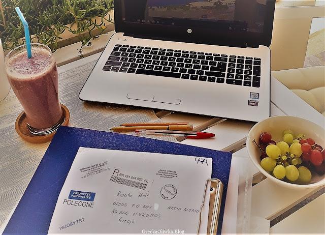 Na stole koktajl, winogrona, zaadresowana korespondencja oraz laptop.