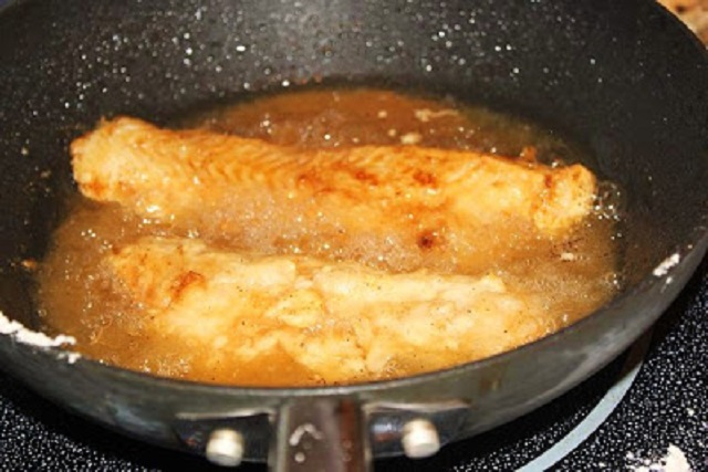 this is fish frying in a fry pan coated with seasoned flour
