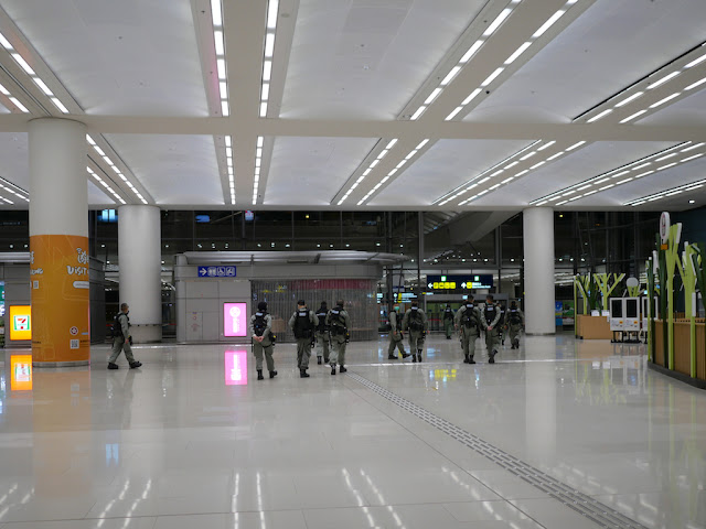 numerous police in riot gear walking through the Hong Kong Port Arrival Hall
