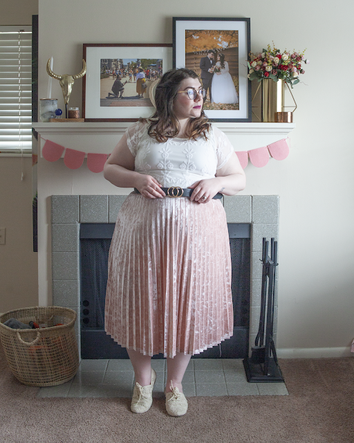 An outfit consisting of white lack short sleeve blouse tucked into a pink velvet pleated midi skirt and cream lace oxford flats.