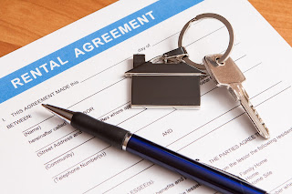 Rental agreement contract on a table with a pen and key on top.