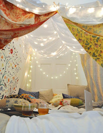 Photograph of a blanket fort with blankets draped on the ceiling with fairy lights and pillows on the floor