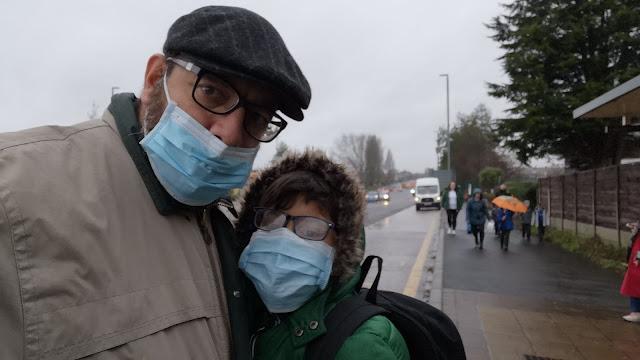 Pai abraçado ao filho, na rua, ambos usando máscara e agasalhos para frio