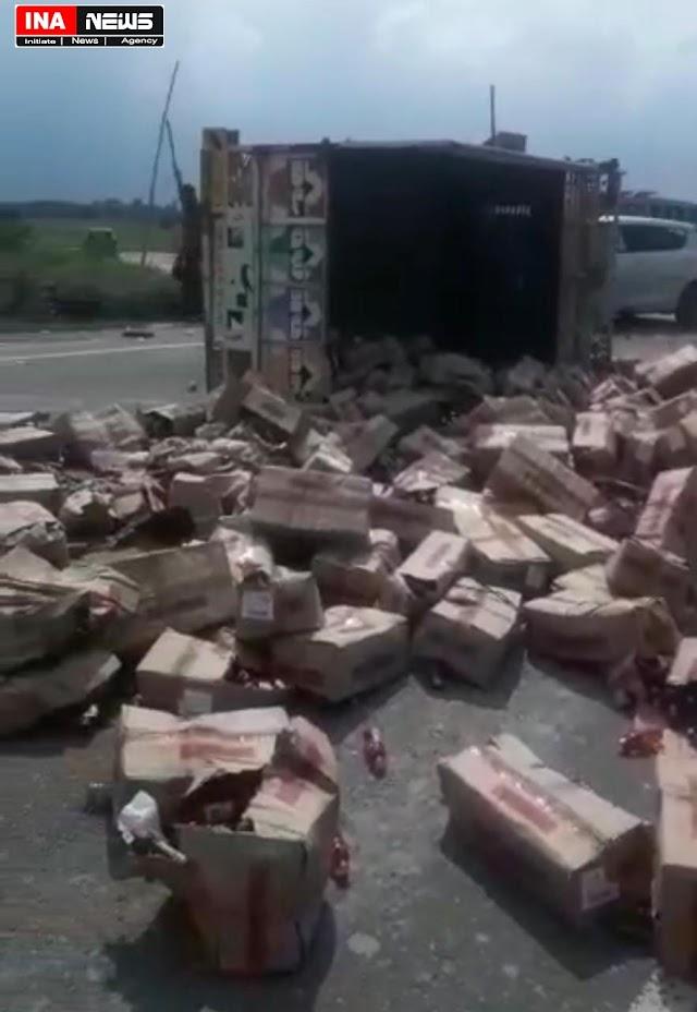 देशी शराब लदा पिकअप का टायर फटने से सड़क पर पलटा, शराब की बिखरे पौवों पर से गुजरते रहे वाहन