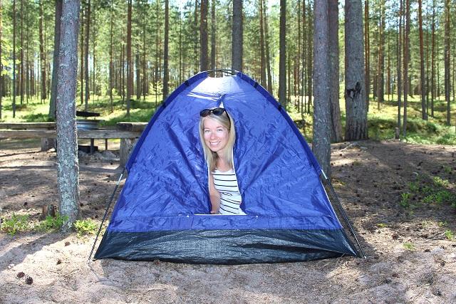 Nainen kurkistaa teltan ovelta