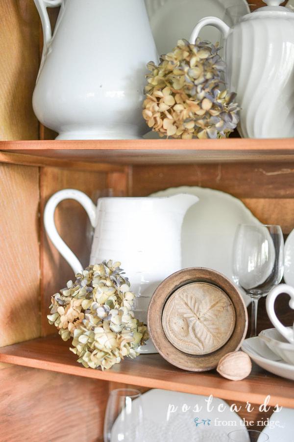 dried hydrangeas, white ironstone, wooden butter molds in antique oak hutch
