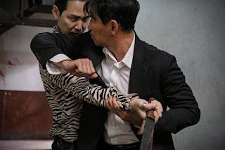 Two men fighting (the man in the suit elbows the man in the striped shirt in the face)