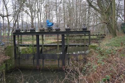 Ein altes, rostiges Stauwehr im Wald mit verrotteten Balken, aber einem neuen, blauen Motor