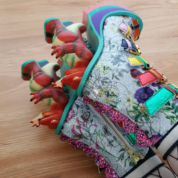 close up of dinosaur heels on boots with floral uppers and glitter spine