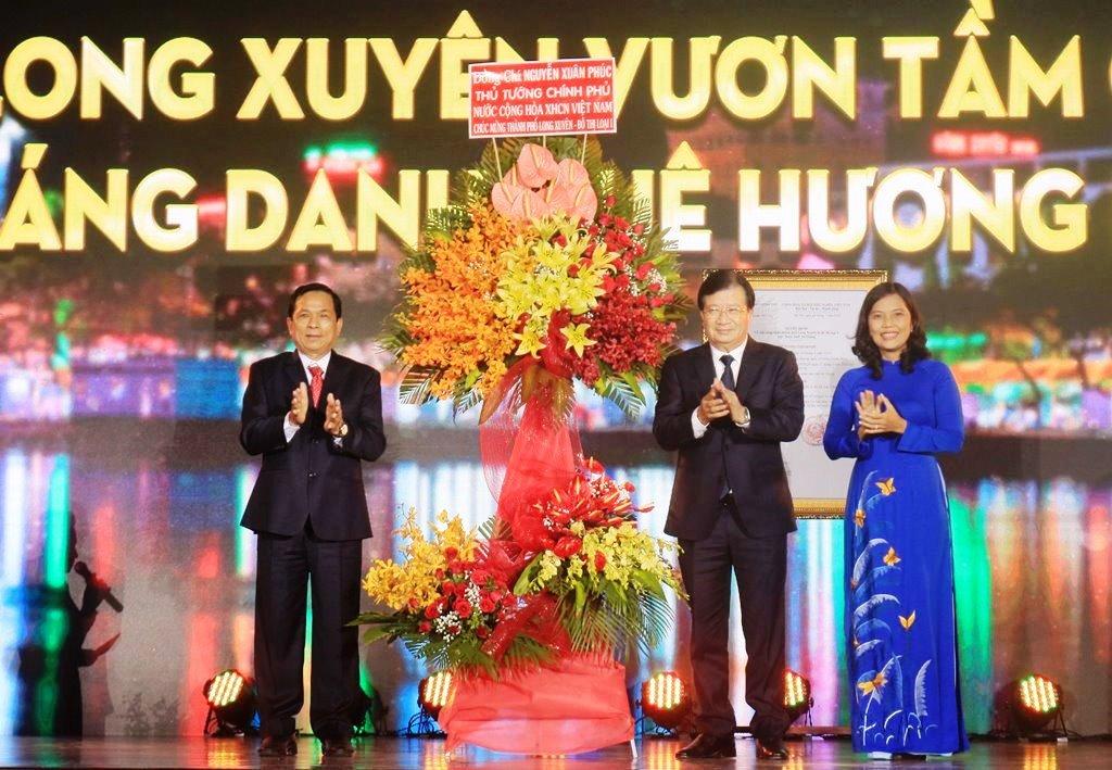 Phó Thủ tướng Chính phủ Trịnh Đình Dũng thay mặt Thủ tướng Chính phủ Nguyễn Xuân Phúc tặng hoa, chúc mừng TP. Long Xuyên đạt đô thị loại I