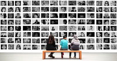 Imagen tomada en una exposición que muestra tres personas sentadas en un banco delante de un mural de numerosas fotos de muchas personas diversas fotografiadas en blanco y negro .